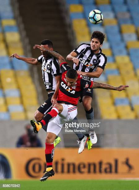Paolo Guerrero of Flamengo struggles for the ball with Rodrigo Lindoso and Igor Rabello of Botafogo during a match between Flamengo and Botafogo part...