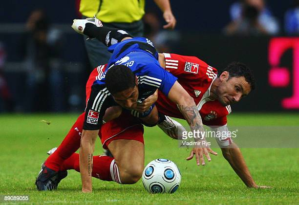 Paolo Guerrero of Hamburg clashes with Mark van Bommel of Bayern during the THome cup match between FC Bayern Muenchen and Hamburger SV at the...