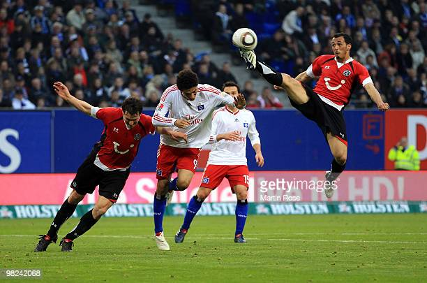 Paolo Guerrero of Hamburg Steven Cherundolo and Mario Eggimann of Hannover compete for the ball during the Bundesliga match between Hamburger SV and...