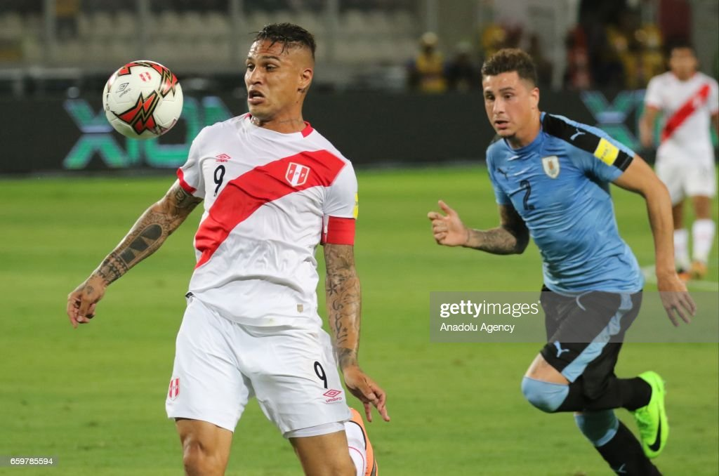 Paolo Guerrero of Peru in action against Jose Gimenez of