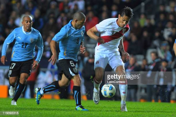 Paolo Guerrero of Peru struggles for the ball with Walter Gargano of Uruguay during a match as part of Finals Quarters of 2011 Copa America at Ciudad...
