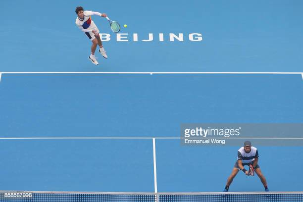 Paolo Lorenzi of Italy and Mischa Zverev of Germany serve during their Men's double semi finals match against Henri Kontinen of Finland and John...