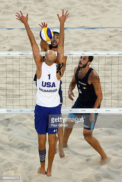 Paolo Nicolai and Daniele Lupo of Italy compete with Phil Dalhausser of United States at the net during the Beach Volleyball Men's Preliminary Pool C...