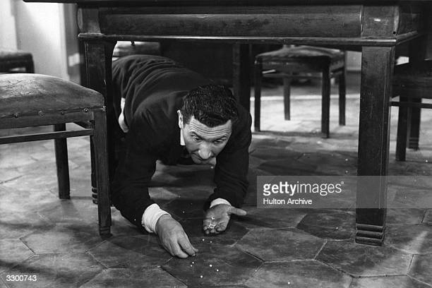 Paolo Stoppa on his hands and knees picking up from under a table in a scene from 'Avarice and Anger' part of the compilation film 'Les Sept Peches...