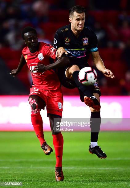 Papa Babacar Diawara of Adelaide United competes with Nigel Boogaard of the Newcastle Jets during the round two ALeague match between Adelaide United...