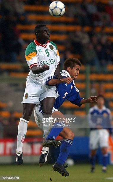 Papa Bouba Diop of Senegal and Junichi Inamoto of Japan compete for the ball during the international friendly match between Senegal and Japan on...