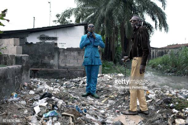 Papa Griffe , a senior and a leader of the Sapeurs walks with his brother Jika in the Mombele area where they live area on February 12, 2012 in...
