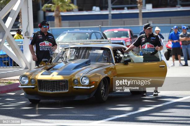 Papa John's Pizza founder and chairman of the board John Schnatter prepares to drive his gold Chevy Camaro Z28 to take on NHRA driver Antron Brown in...