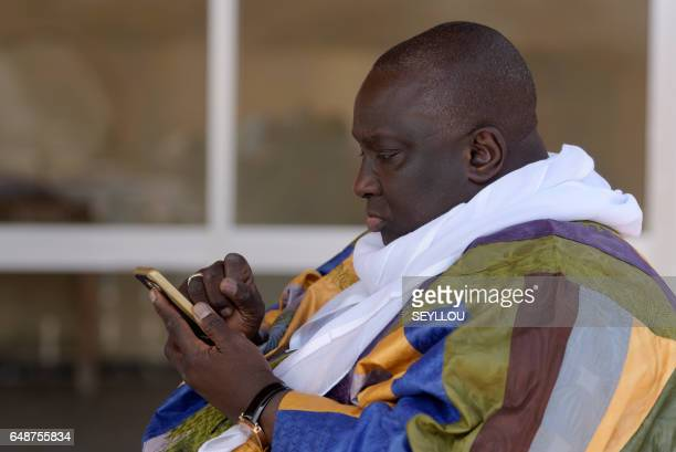Papa Massata Diack son of former president of the International Association of Athletics Federations Lamine Diack looks at a mobile phone during an...