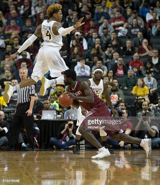 Papa Ndao of the Saint Joseph's Hawks drives past Justin Tillman of the Virginia Commonwealth Rams in the championship game of the men's Atlantic 10...