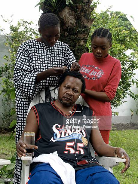 Papa Wemba a world famous music artist and the most famous living artist in the Congo gets his hair done in his garden on February 28 2002 in...