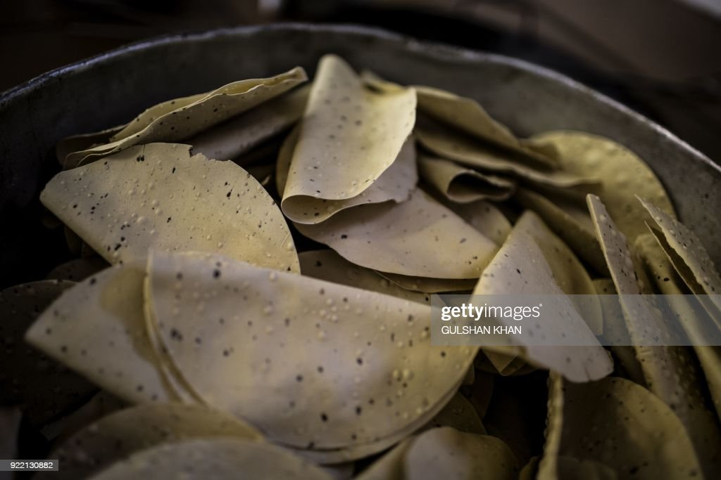 Papadums, an Indian side dish, is prepared in a pan at the Geet Restaurant on February 20, 2018 in Pretoria. The restaurant is the choice caterer for the Indian cricket team during their visits to play in South Africa. /