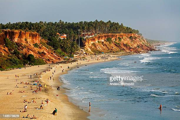 Papanasham beach ringed by red laterite cliffs.