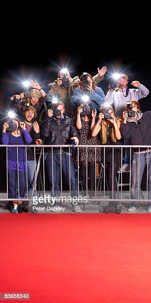 Paparazzi behind railings and red carpet