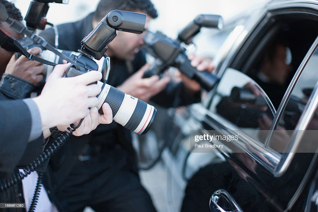 Paparazzi holding camera lens to car window : Stock Photo