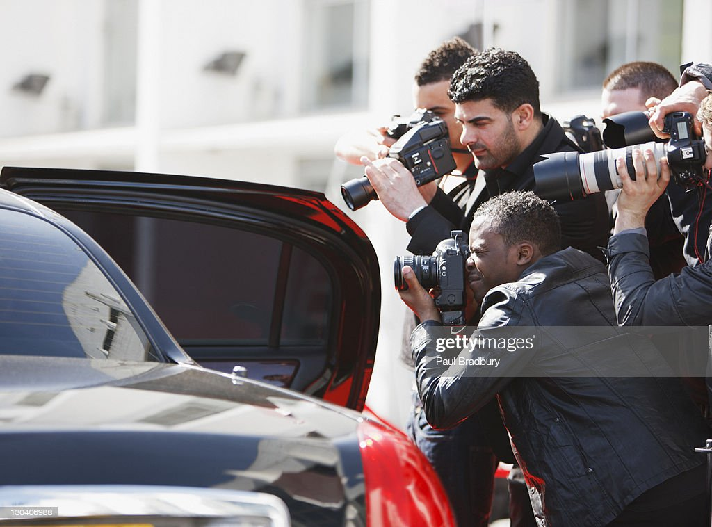 Paparazzi taking pictures of celebrity in car : Stock Photo