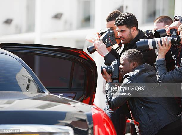 Paparazzi taking pictures of celebrity in car