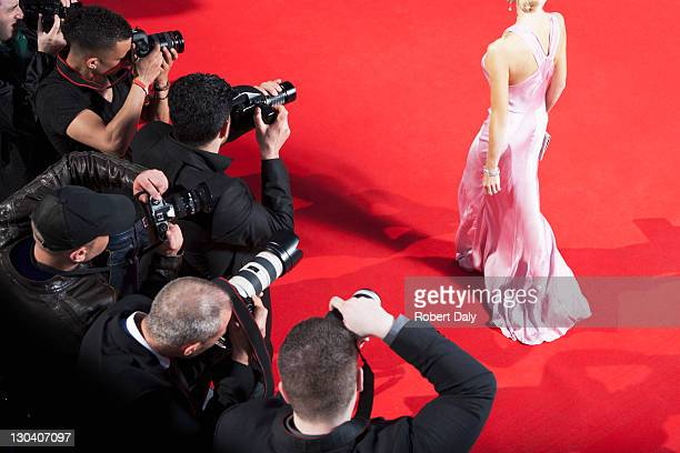 paparazzi taking pictures of celebrity on red carpet - beroemdheden stockfoto's en -beelden