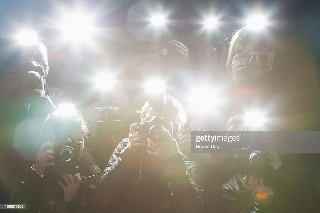 Paparazzi taking pictures with flash : Stock Photo