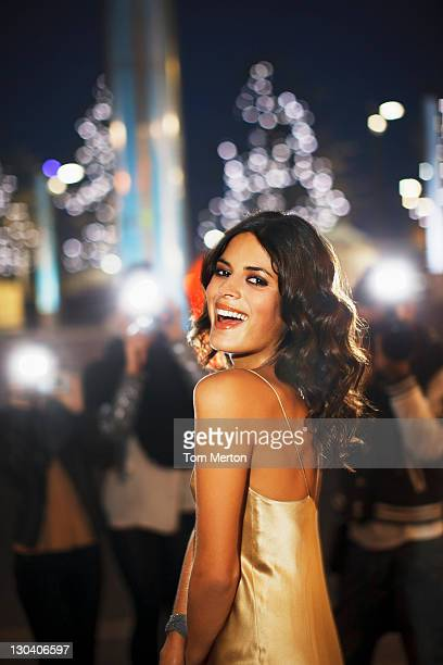 paparazzi taking smiling celebrity's picture - evening gown stock photos and pictures