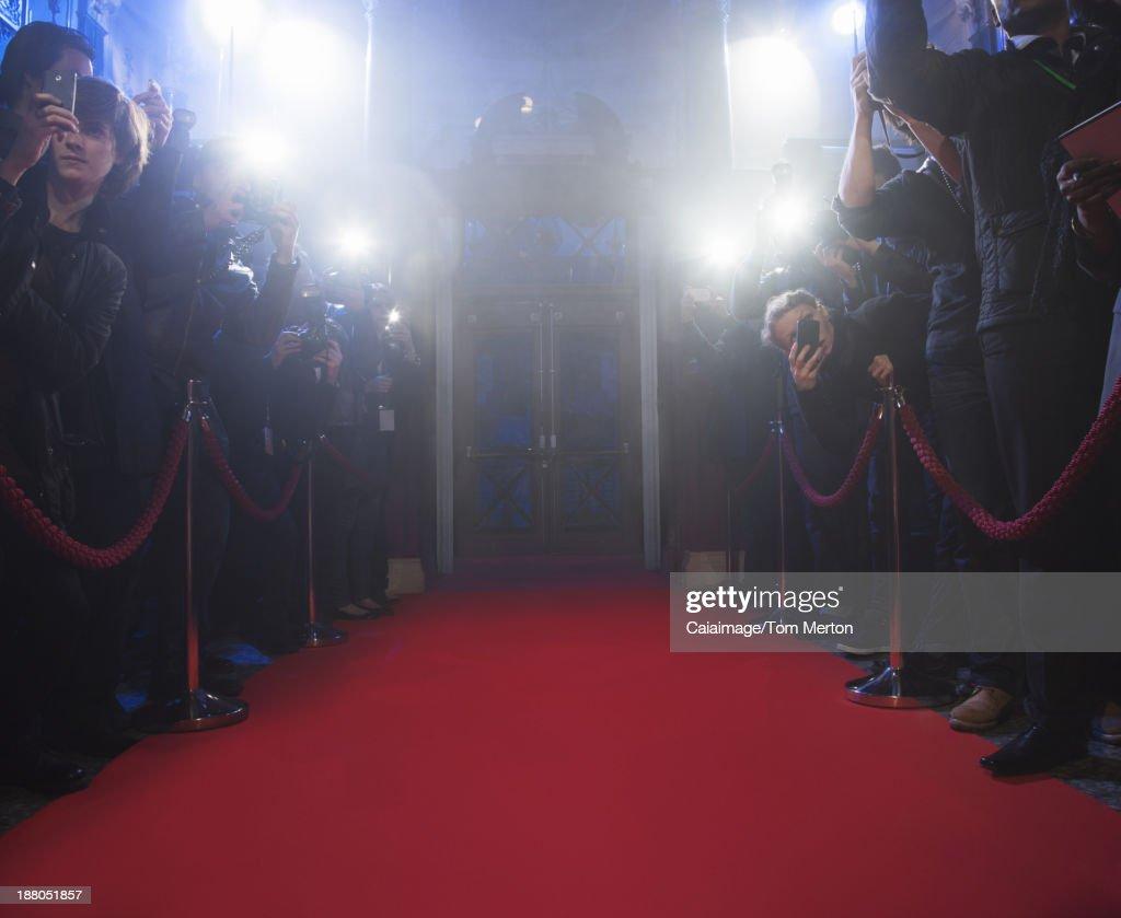 Paparazzi using flash photography along red carpet : Stock Photo
