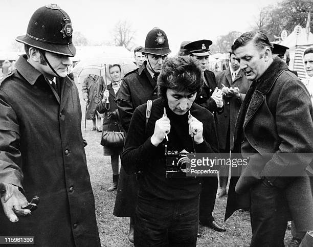 Paparazzo Ray Bellisario being escorted out of the Badminton Horse Trials by police after a traffic accident involving Princess Margaret and her...
