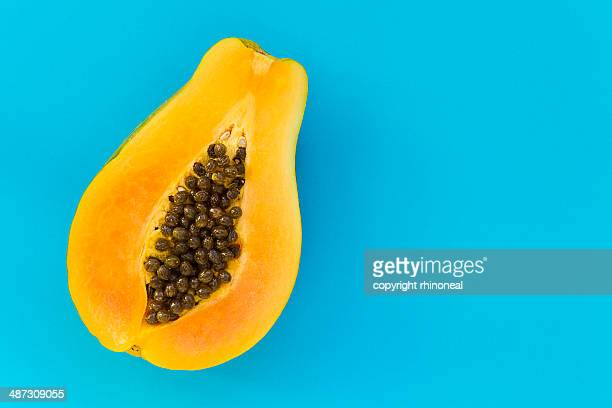 papaya on a blue background - papaya stock photos and pictures
