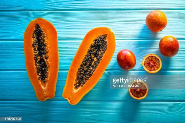 papaya abierta en dos y naranjas de sangre - exotismo fotografías e imágenes de stock