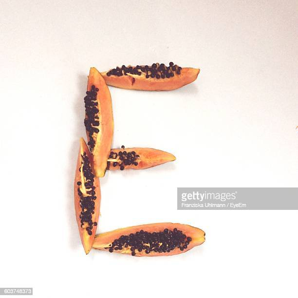 Papaya Slices Arranged In Letter E Against White Background