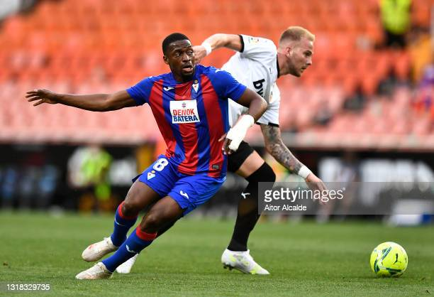 Pape Diop of SD Eibar battles for possession with Uros Racic of Valencia CF during the La Liga Santander match between Valencia CF and SD Eibar at...