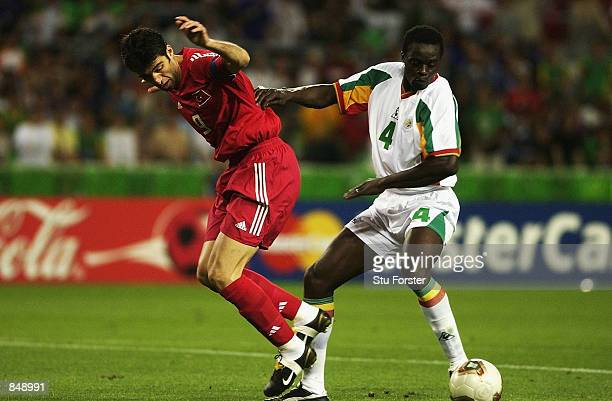 Pape Malick Diop of Senegal wins the tackle against Hakan Sukur of Turkey during the FIFA World Cup Finals 2002 Quarter Finals match played at the...