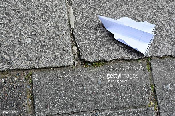 Paper Aeroplane Lying Upside Down on the Pavement