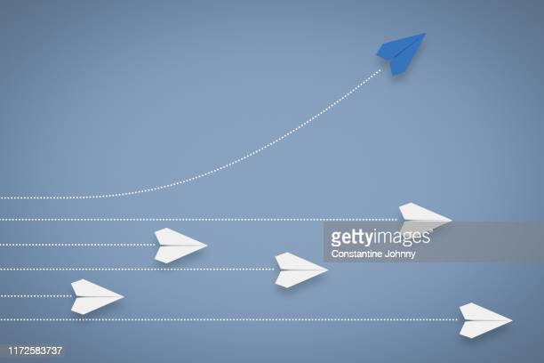 paper airplane different direction and approach. think different & leadership concept. - inspiration stock-fotos und bilder