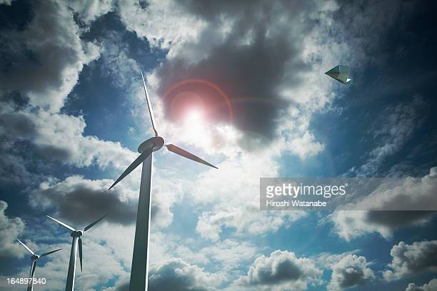 Paper airplane flying above the wind farms