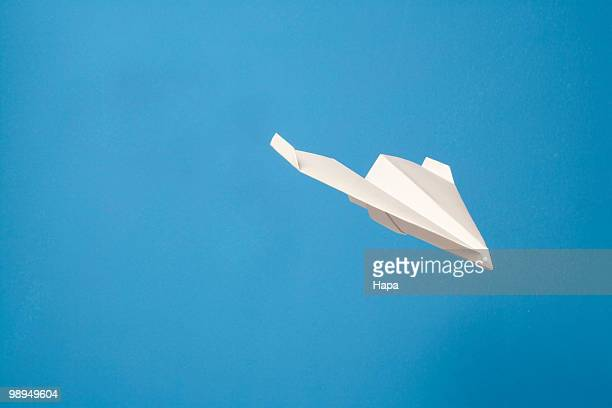 Paper airplane gliding through air