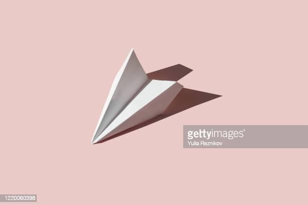 paper airplane on the pink background - concepts et thèmes photos et images de collection