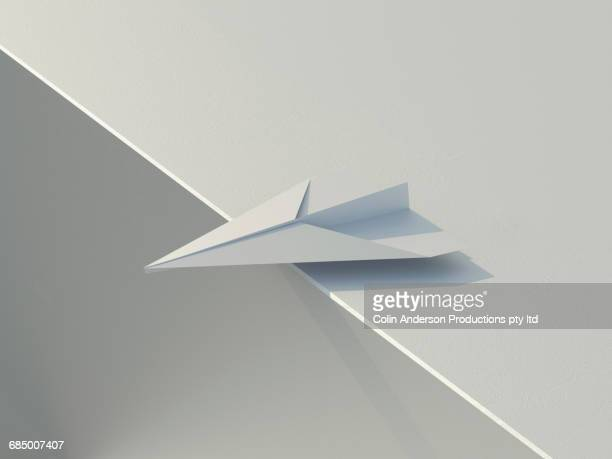 Paper airplane teetering on an edge