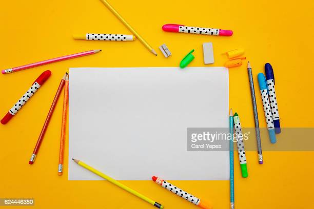 paper and color pens in a yellow background - colouring book stock photos and pictures