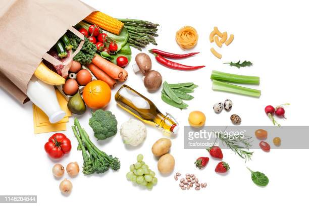 paper bag full of different food on white background - fruit stock pictures, royalty-free photos & images