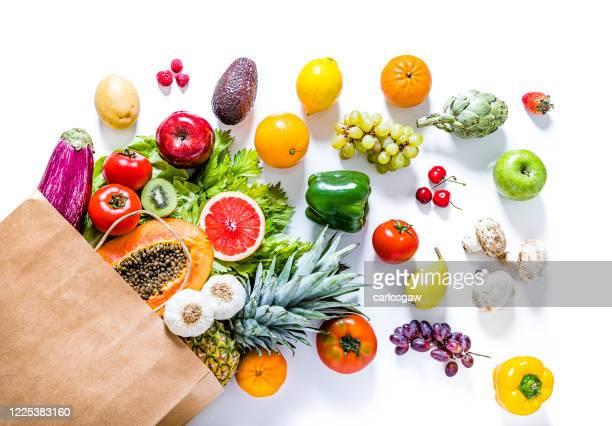 bolsa de papel llena de varios tipos de frutas y verduras sobre fondo blanco - fruta fotografías e imágenes de stock