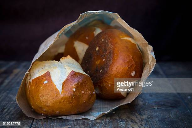 Paper bag with pretzel rolls on wooden table