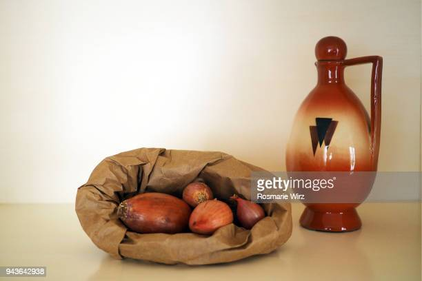 paper bag with red onions and oil bottle on white - bottle stopper stock photos and pictures