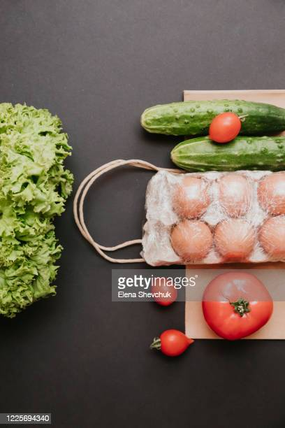 paper bag with vegetables.cucumbers, tomatoes, vegetable oil, eggs and salad isolated on black background.food supplies crisis food stock for quarantine.food delivery, donation, coronavirus.tape measure. - odessa crisis stock pictures, royalty-free photos & images
