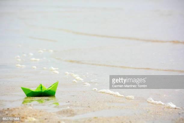 paper boat and at the seashore. - pessoa desalojada - fotografias e filmes do acervo