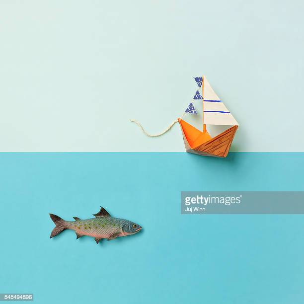 Paper boat and toy fish