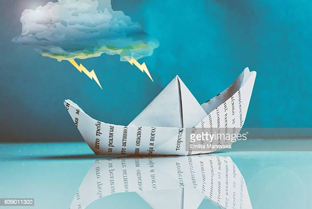Paper boat sailing in storm