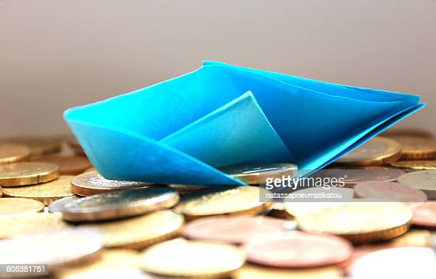 Paper boat sinking in a sea of euro coins