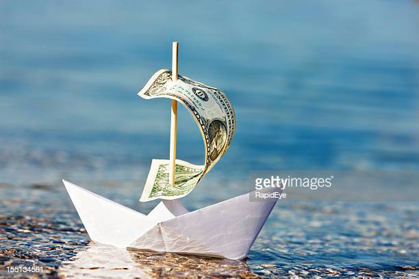Paper boat with $1 bill sail is blown onshore