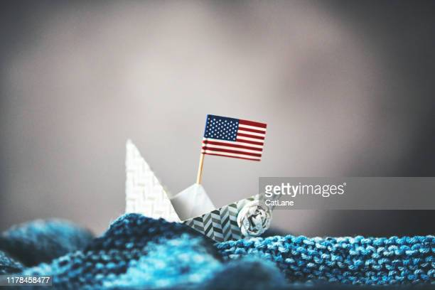 paper boat with american flag on handmade waves with stormy sky - american flag ocean stock pictures, royalty-free photos & images