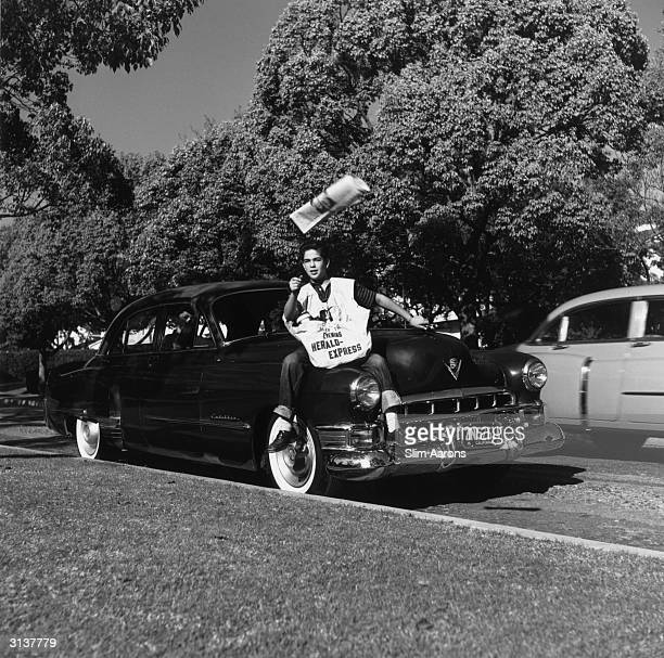 Paper boy Steve Reed being given a ride on the bonnet of his mother's Cadillac to do his paper round